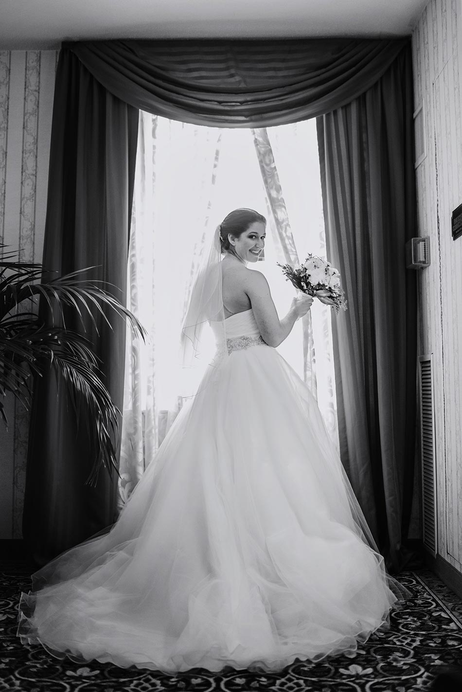 bride in ballgown in front of window St Paul Hotel winter wedding mn