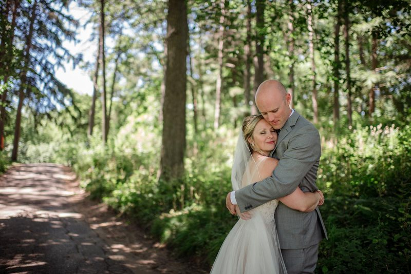 bride and groom hold each other sweetly before their Theodore Wirth Chalet Wedding