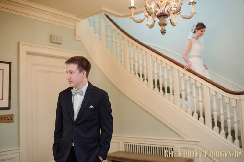 The bride comes down the stairs of the St Paul College Club lobby to see her groom for the first time.