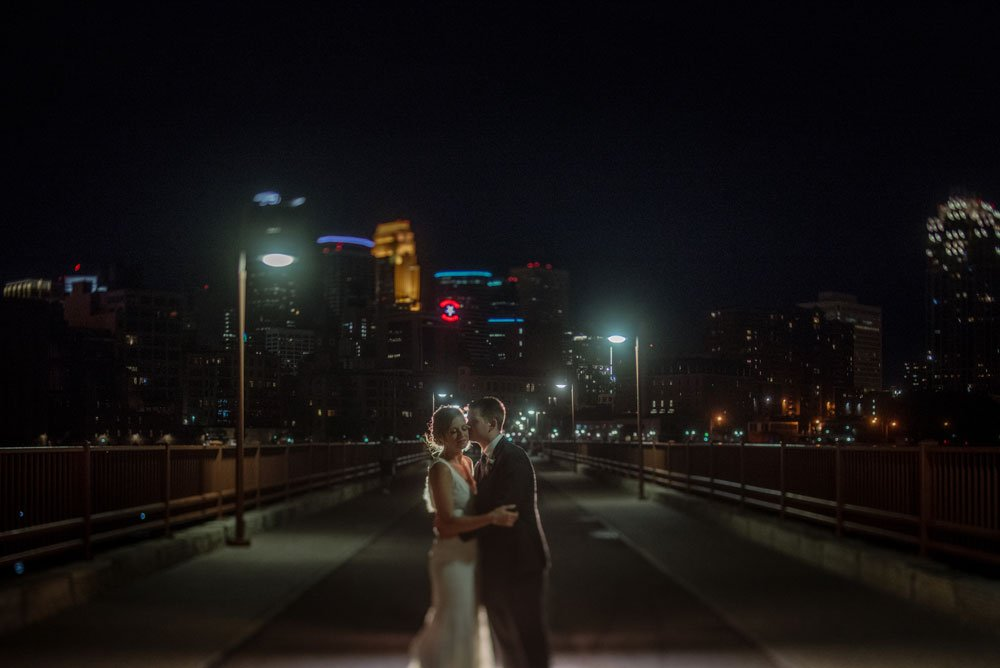 couple at night on stone arch bridge minneapolis