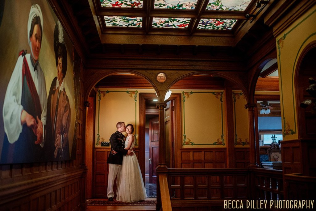 couple  embrace by stairs inside Van Dusen Mansion Wedding Minneapolis