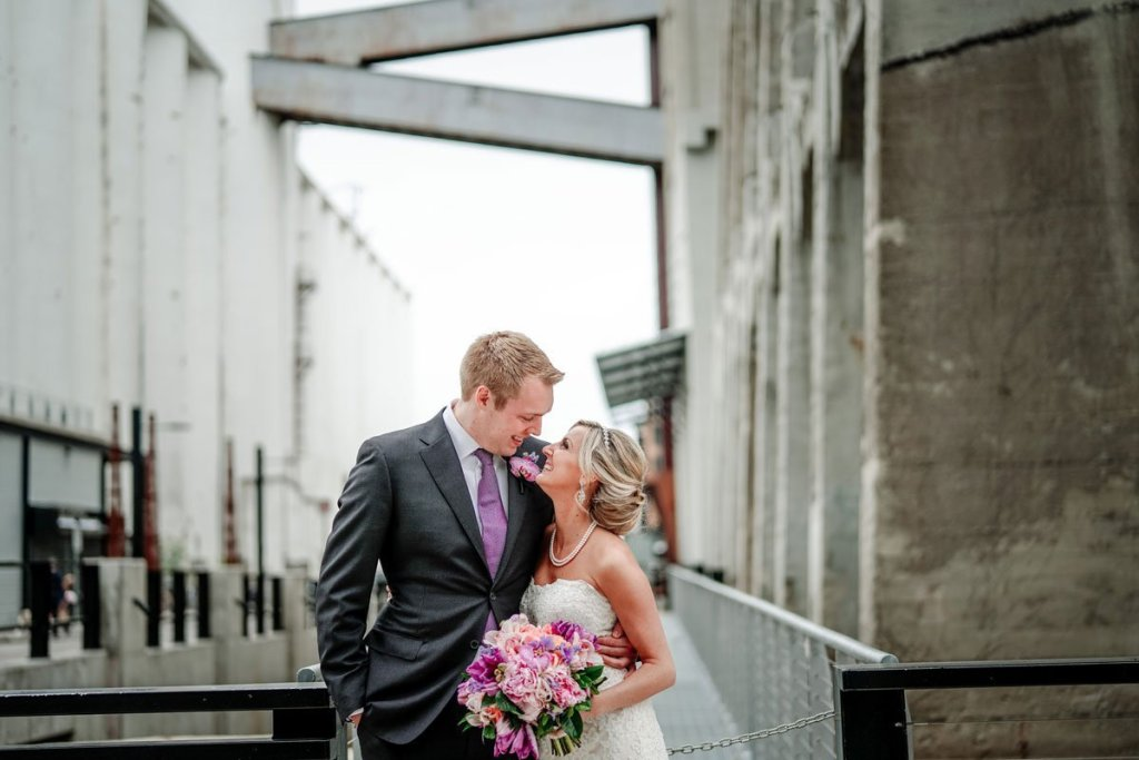 bride and groom with pink details embrace behind machine shop venue minneapolis
