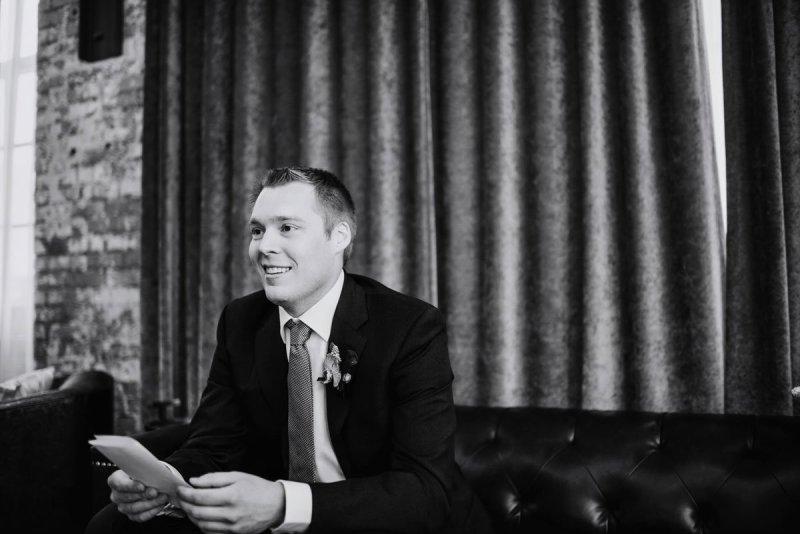 groom reads note before Machine shop wedding ceremony