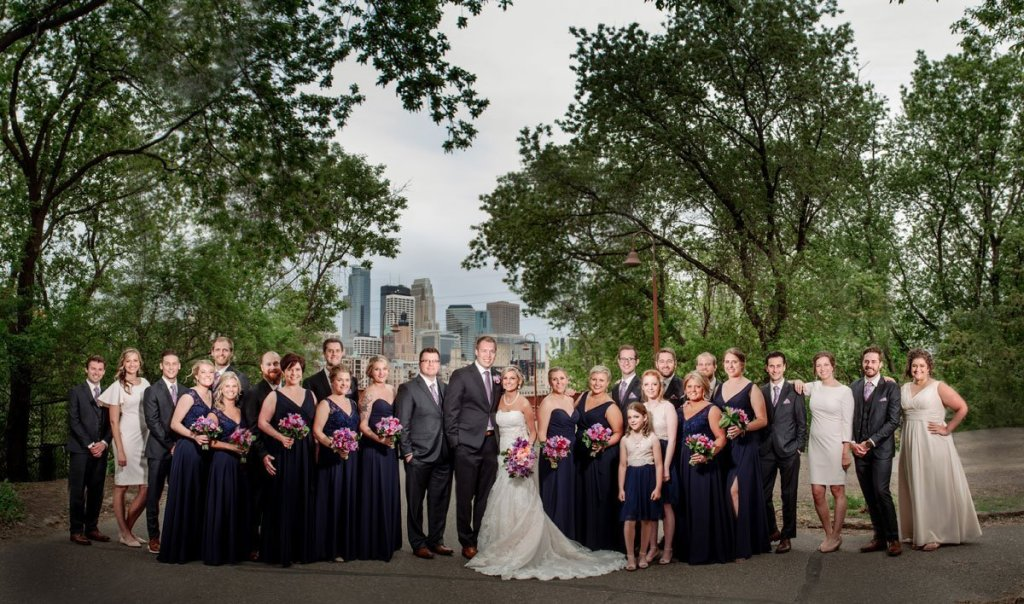 large wedding party in front of stone arch bridge in Minneapolis