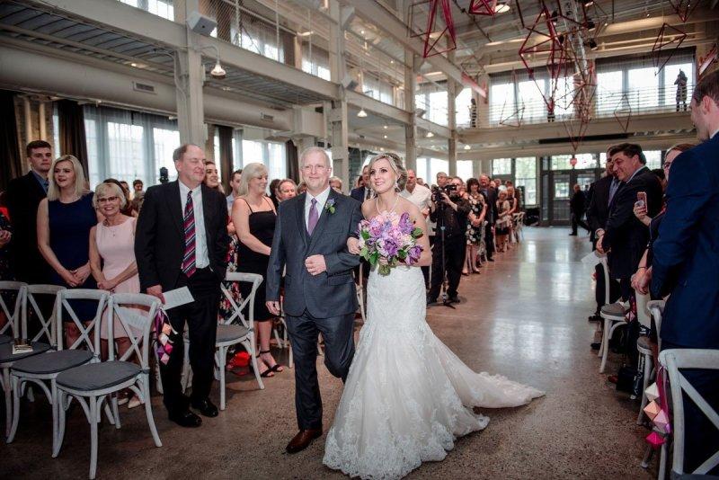 Dad and bride walk down aisle in Machine shop wedding