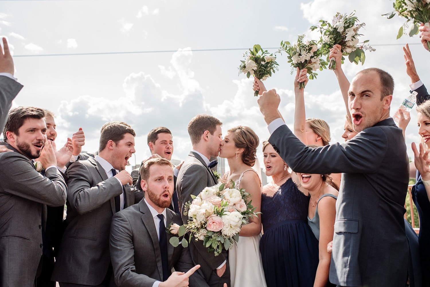 excited wedding party hoots by couple