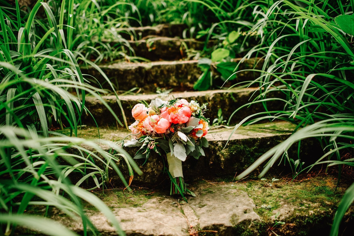 wedding bouquet on stone steps of hilltop venue in spring green