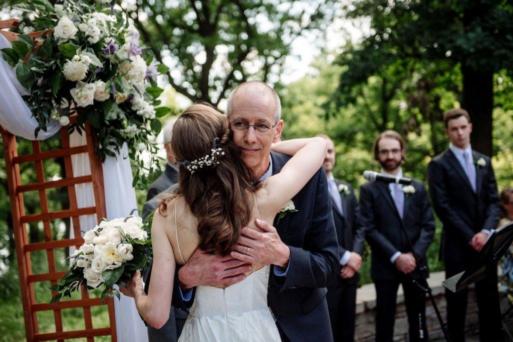 bride hugs daughter at silverwood park wedding mn