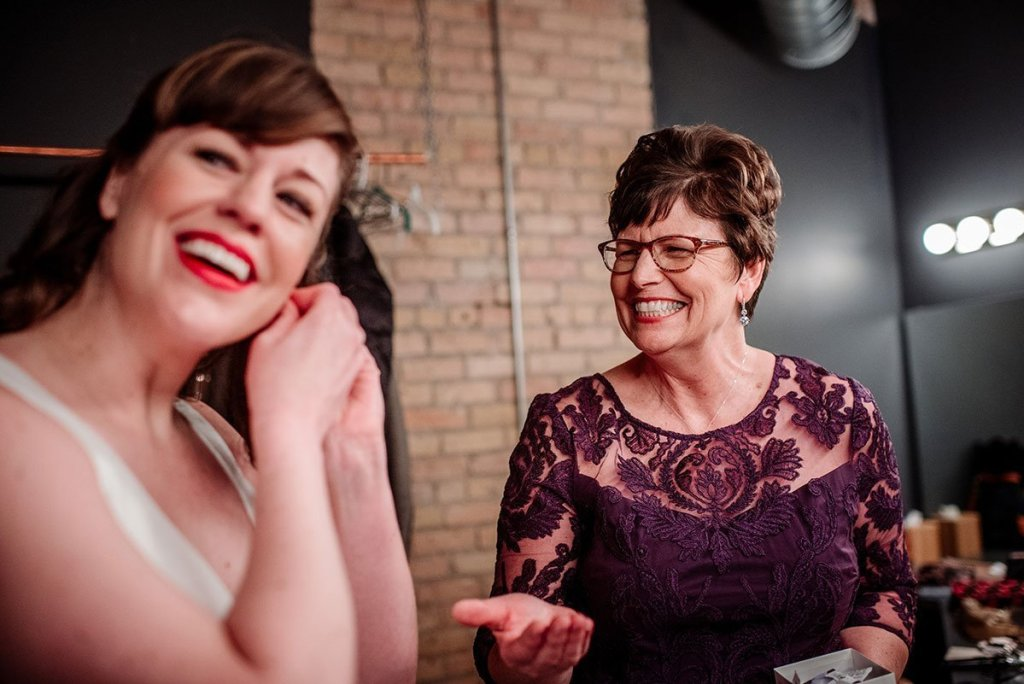 bride laughing with mom while getting ready at solar arts