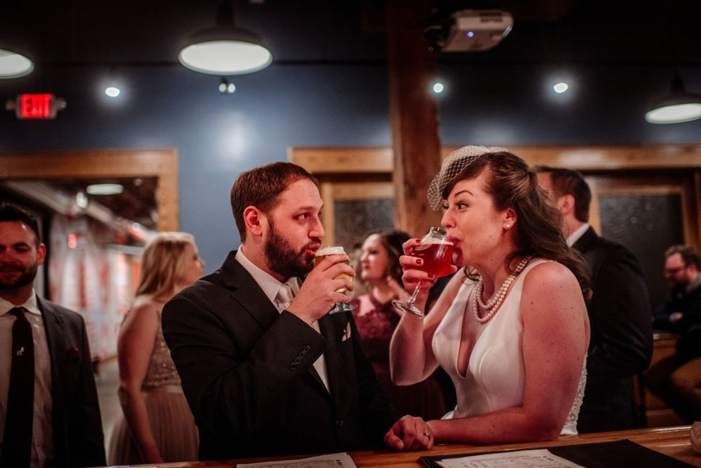bride and groom share a beer at indeed brewing at solar arts