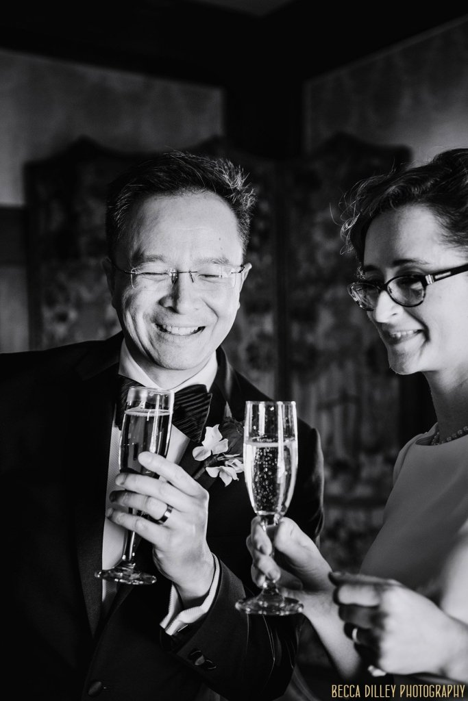 couple laugh while holding champagne classes in minneapolis mansion before elopement