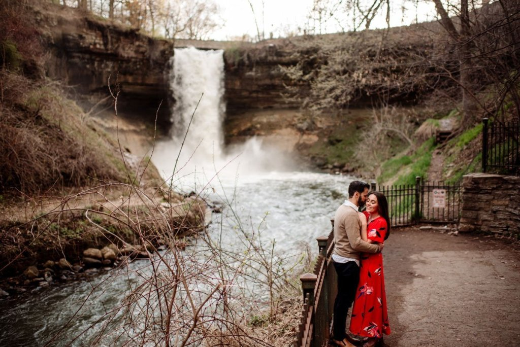 far away portrait of couple at minnehaha falls in minneapolis with waterfall behind them