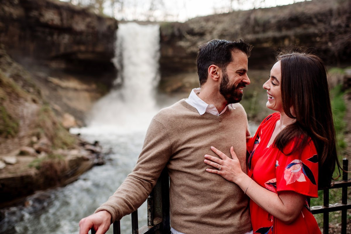 couple having fun at minnehaha falls for portraits by the waterfall in minneapolis summer