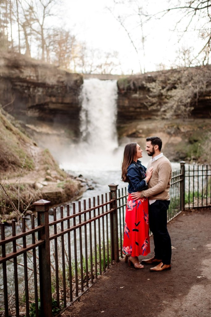 standing couple having fun at minnehaha falls for portraits by the waterfall in minneapolis summer