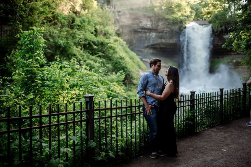 moody portrait of couple by fence with minnehaha falls behind them