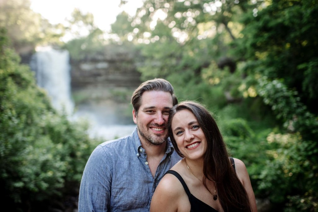 portrait of couple sitting next to each other with minnehaha falls behind them
