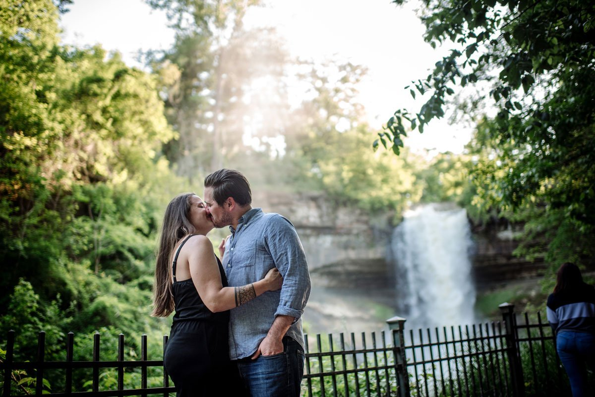 portrait of couple kissing by fence with minnehaha falls behind them