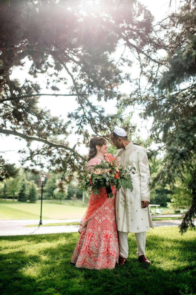 bride in red sari and groom in traditional white hindu outfit hold each other under trees before hindu jewish wedding ceremony