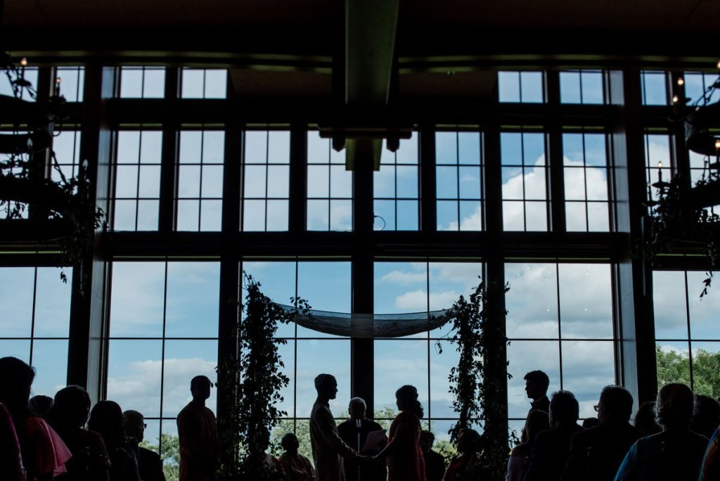wedding ceremony in front of large windows with chuppa in silhouette in Minnesota