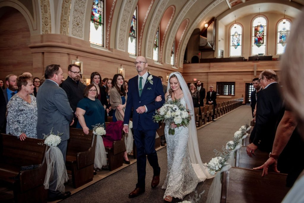 bride and her father walk down aisle of large church in mn