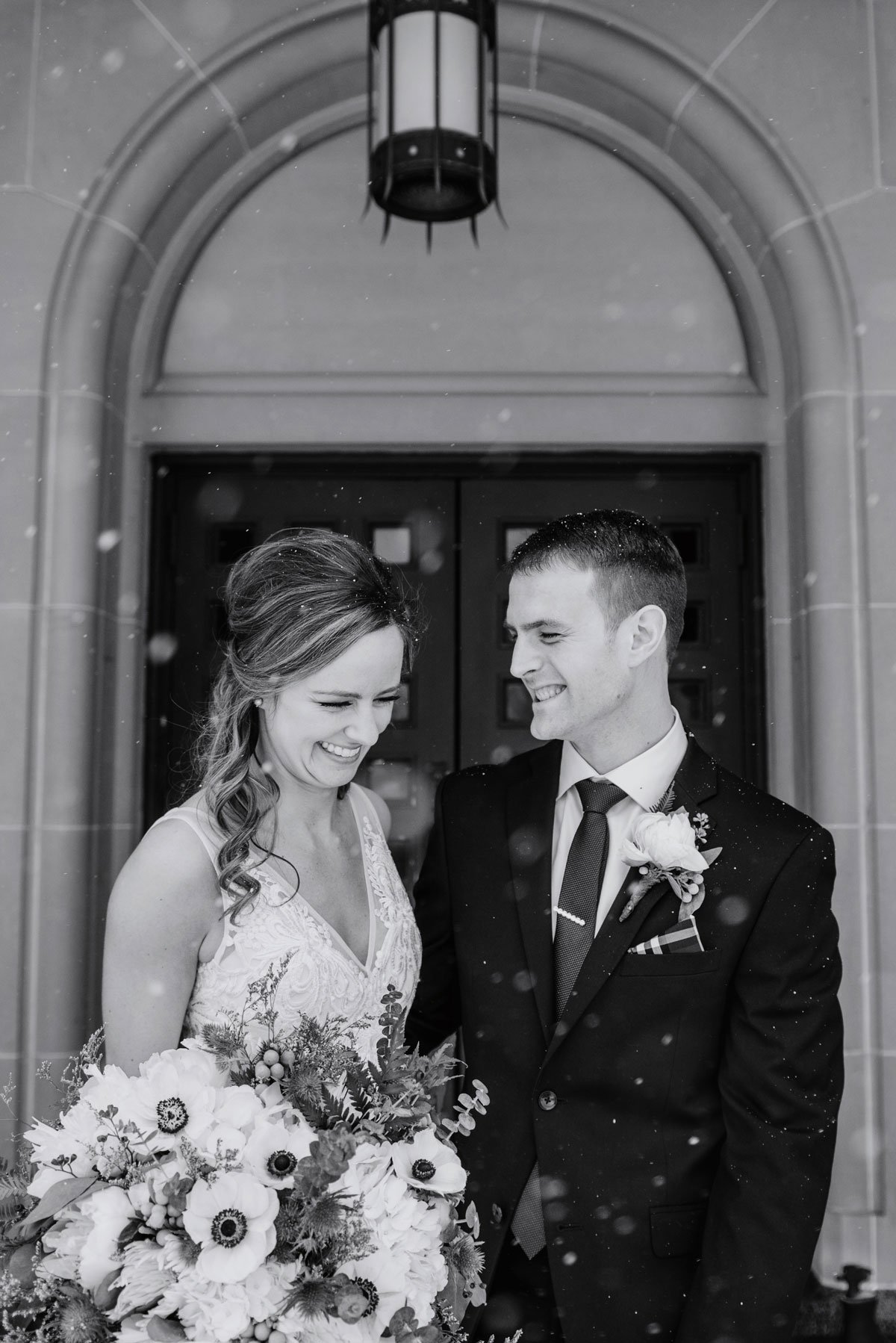 black and white photo of couple in snowy weather with church door behind them