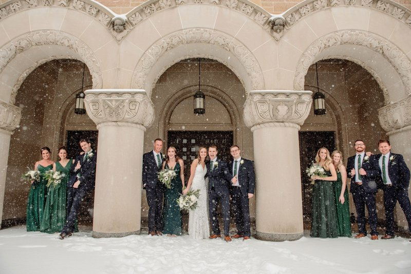 header image of wedding party outside in a snowstorm under the arches of a church while snow whips past