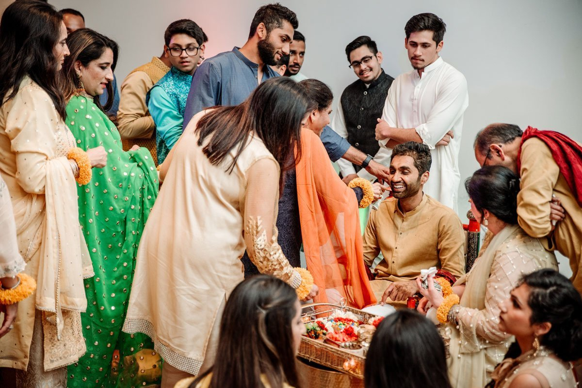 the groom is decorated with turmeric paste for his muslim pakistani wedding at Weisman Art Museum