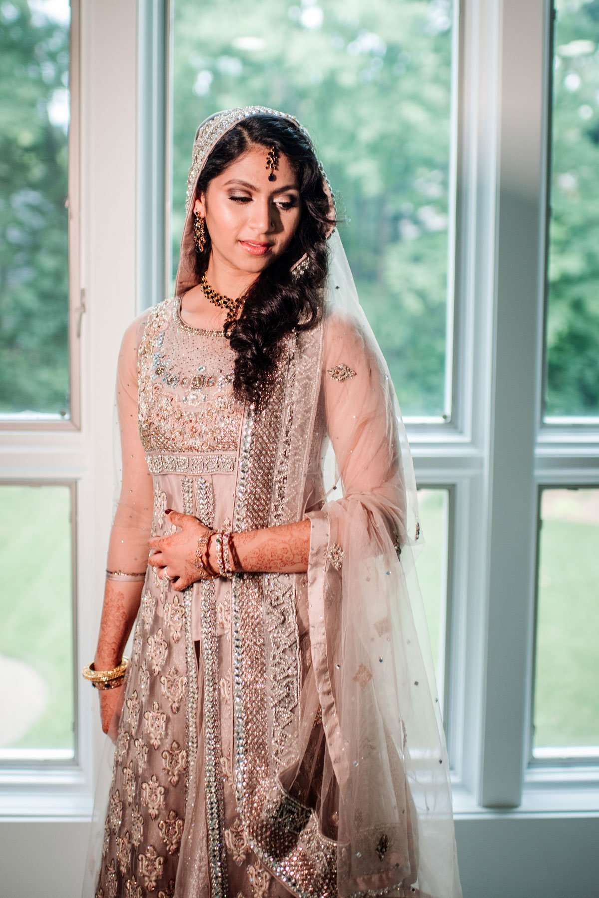 Bride in front of window with rose gold sari in Minneapolis