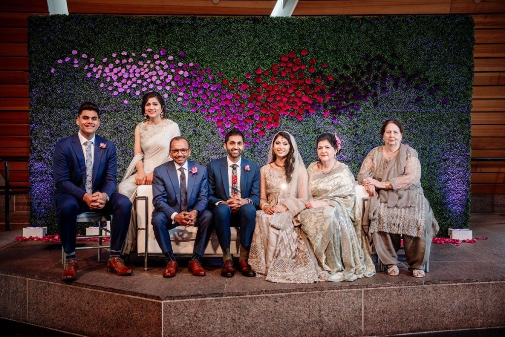 The whole family in front of a floral wall installation at Muslim Pakistani wedding at McNamara Center in Minneapolis
