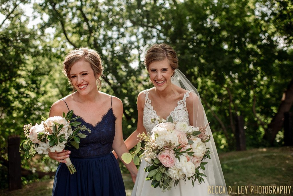 maid of honor and bride share a laugh in front of green trees minneapolis