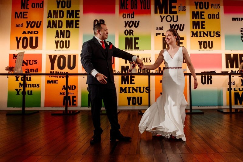 first dance with posters behind them esker grove wedding at the walker art center minneapolis
