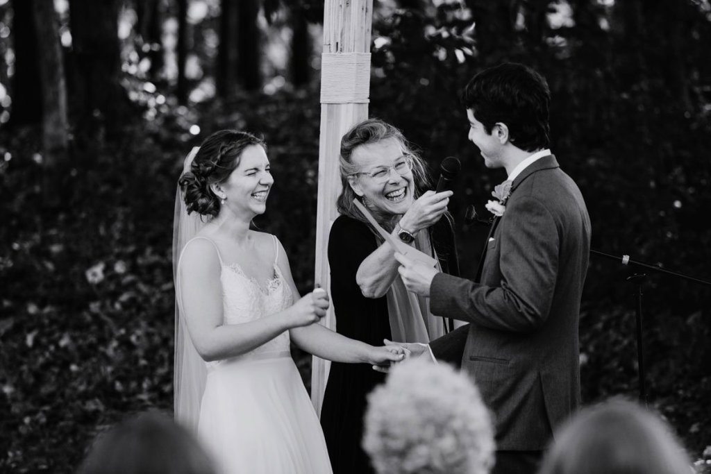 bride laughts during vows - image in black and white voyageur wedding environmental center mn