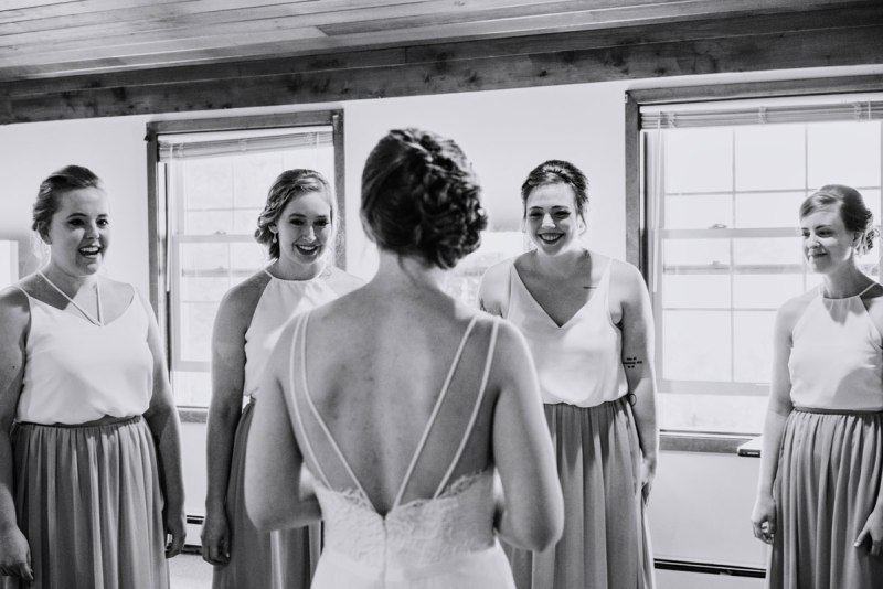 bridesmaids react to seeing bride for first time in her dress voyageur wedding environmental center mn