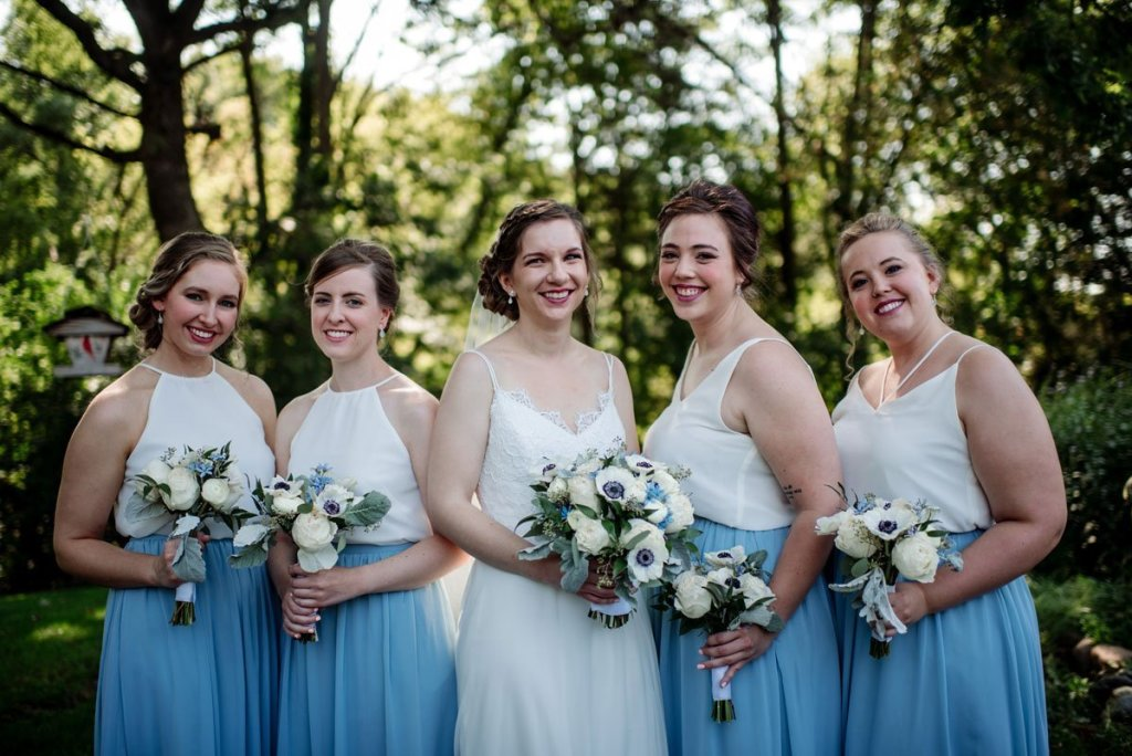 4 bridesmaids with white tops and blue skirts voyageur wedding environmental center mn