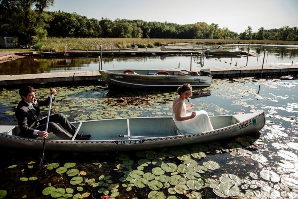 bride and groom get into a canoe during wedding voyageur in MN