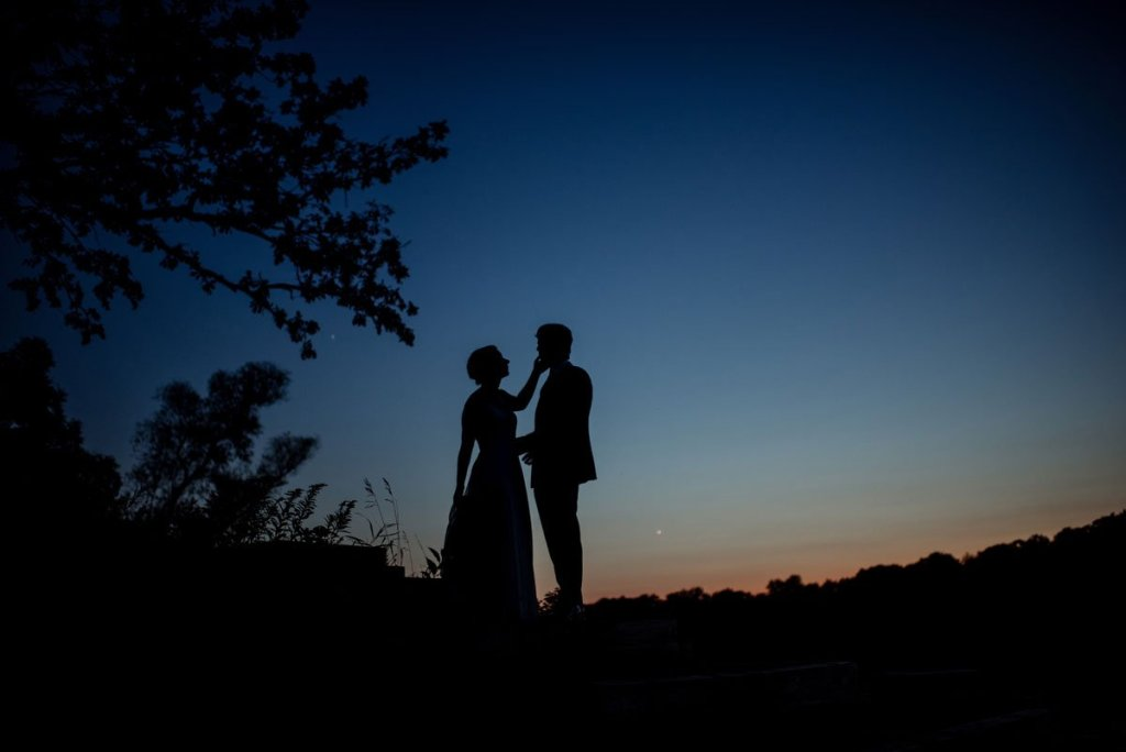 silhouette of bride touching groom's face against sunset at voyageur wedding environmental center mn