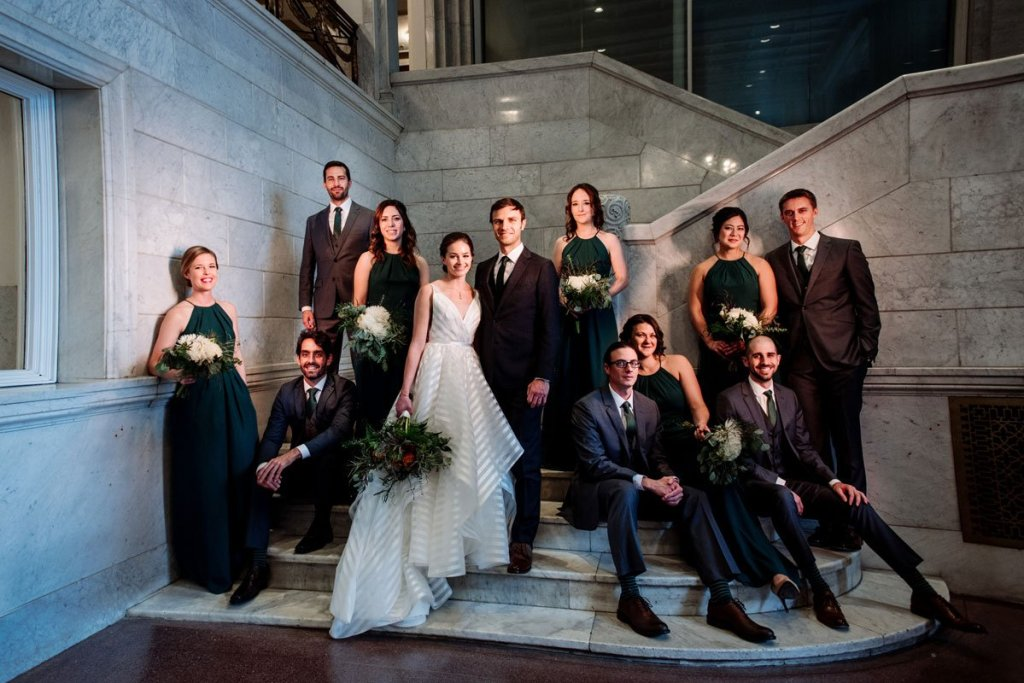 wedding party on stairs inside lumber exchange minneapolis with flash composite lighting for dramatic photography