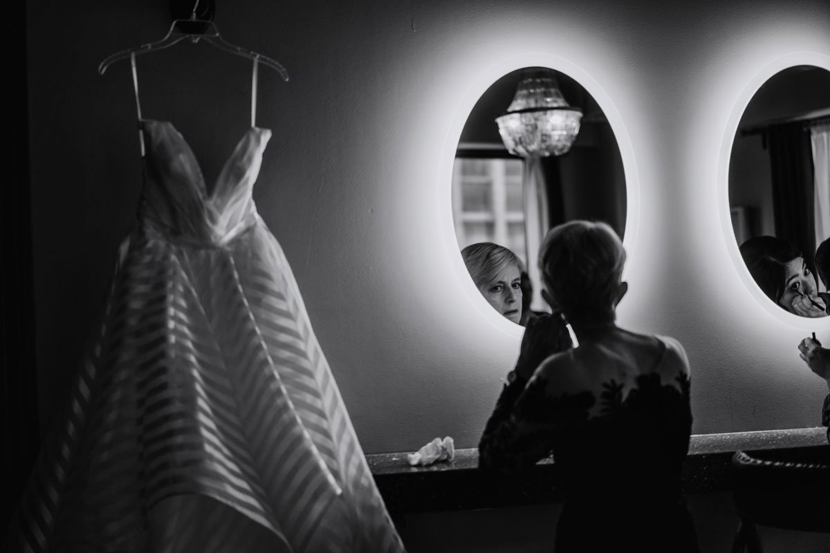 black and white image of wedding dress handing at lumber exchange before wedding while mom looks in mirror