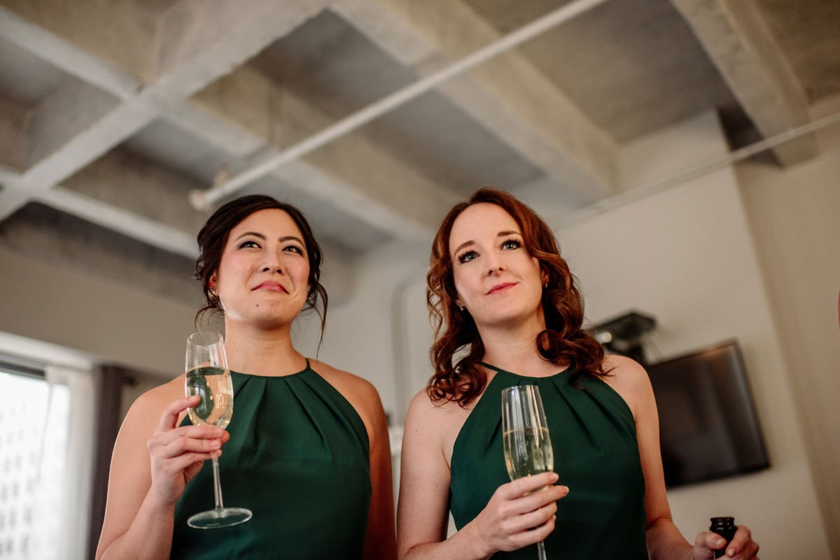 bridesmaids look emotional as they watch the bride finish getting ready before lumber exchange wedding minneapolis
