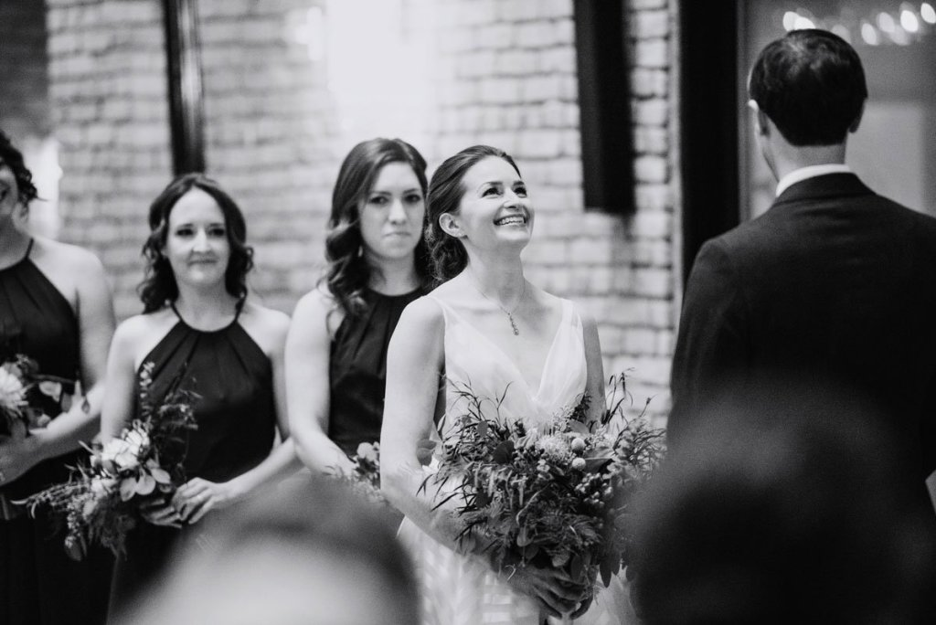 Bride laughs during wedding ceremony at lumber exchange
