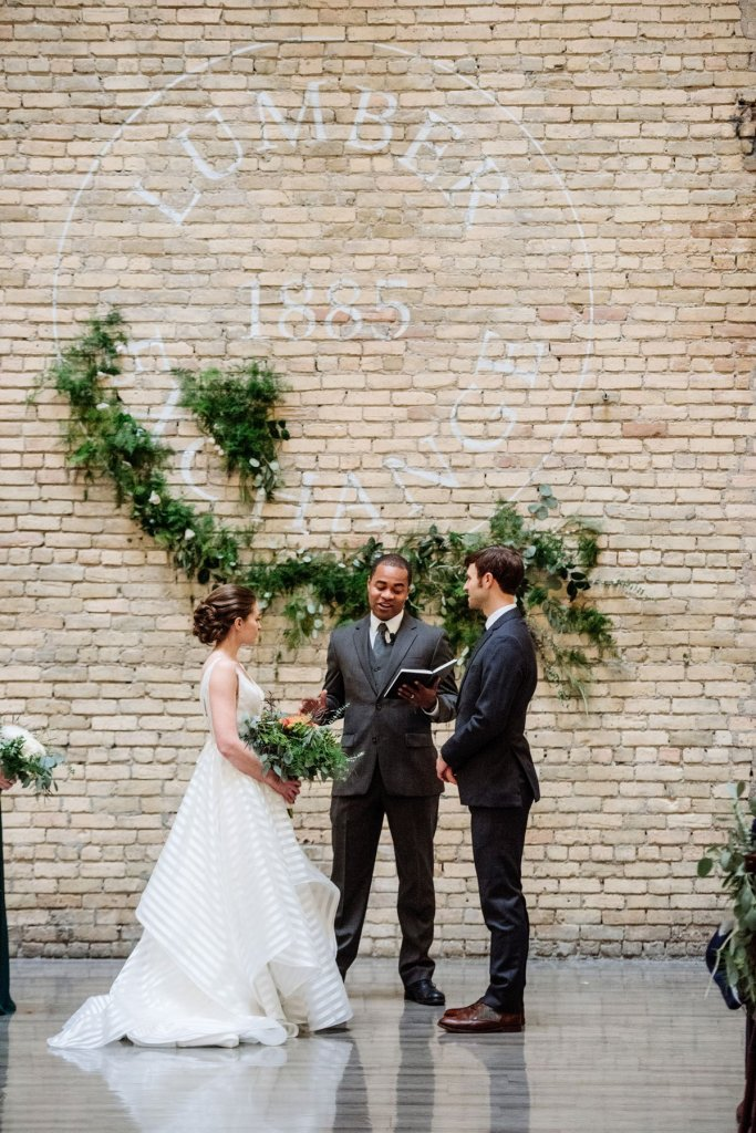 bride and groom exchange vows under large green swagged floral installation at lumber exchange