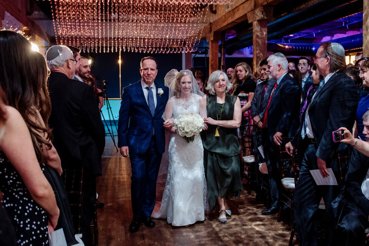bride and her parents walk down aisle at new years eve wedding Minneapolis event center