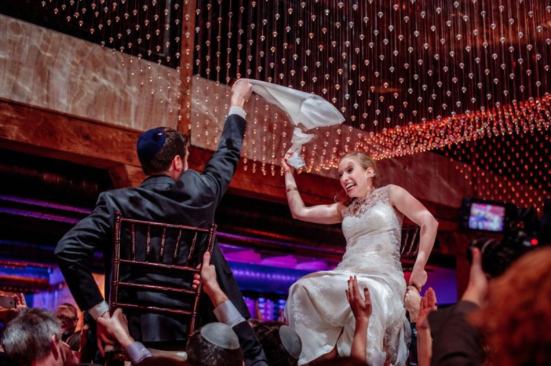 dancing the hora up in chairs, the bride and groom share a napkin new years eve wedding Minneapolis event center