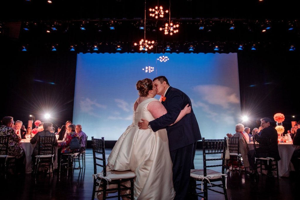 couple kiss on stage with blue skies backdrop washington pavilion wedding sioux falls