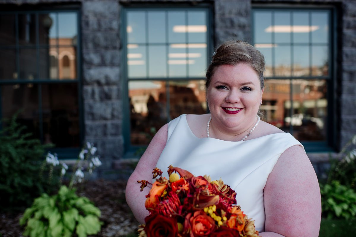bride with bright orange and red flowers outside washington pavilion wedding sioux falls