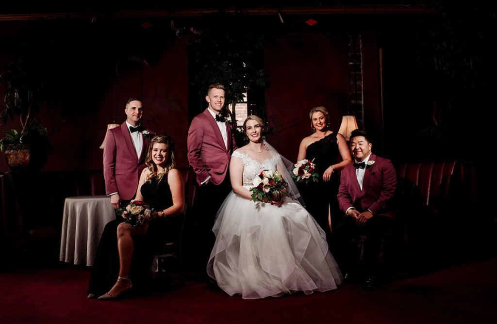 flash composite of wedding party with 2 groomsmen and 2 bridesmaids in maroon with dramatic lighting in minneapolis loring restaurant