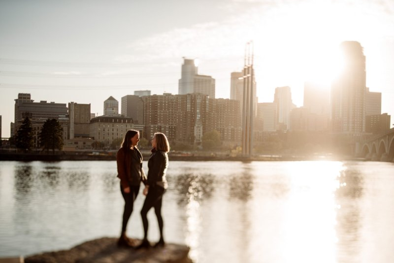 couple in silhouette with Minneapolis skyline behind them at golden hour