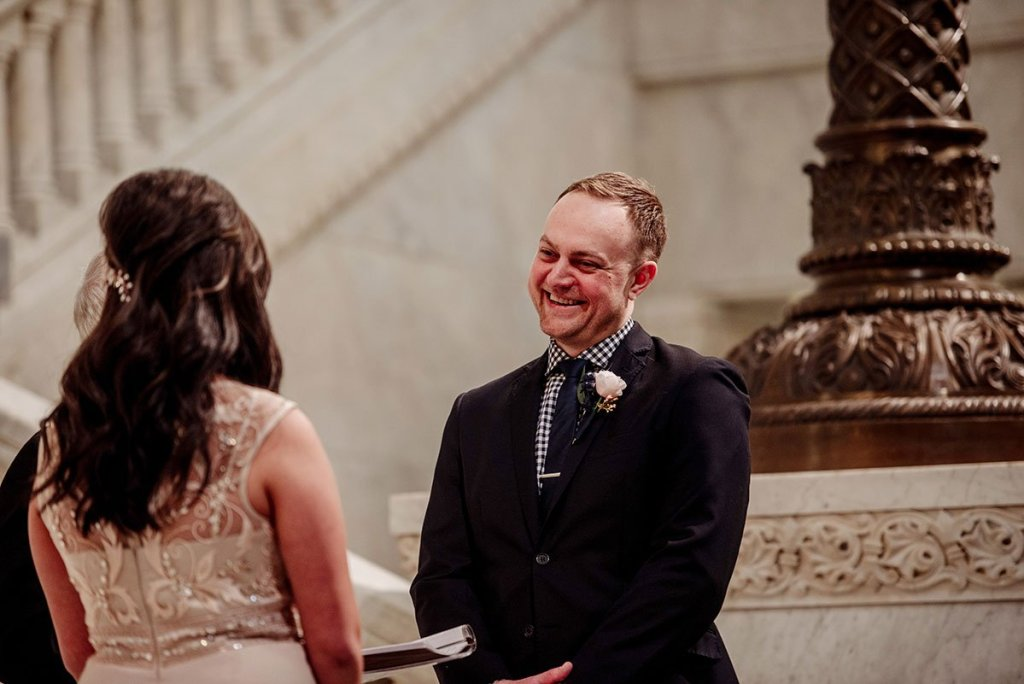 groom smiles as he looks at bride during small wedding at minneapolis city hall