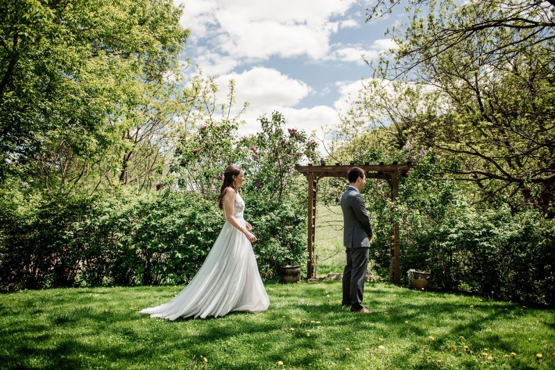 bride and groom getting see each other for first look at wedding at round barn