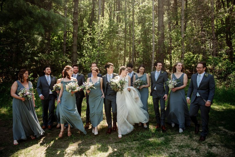 wedding party walks through woods at round barn wedding